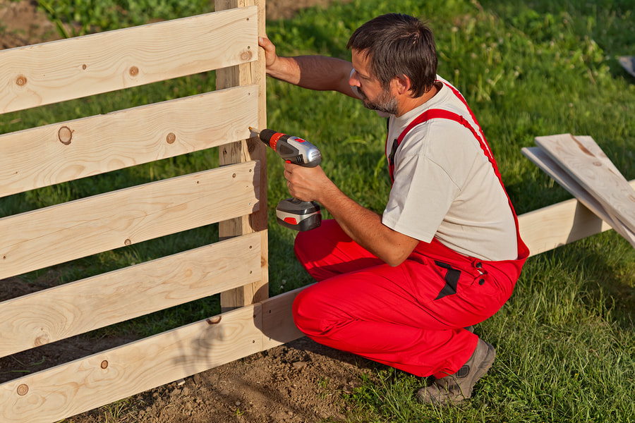A man installing a wood fence